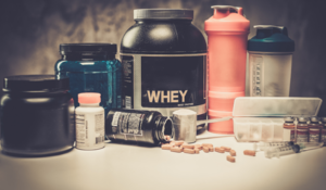 Supplements displayed on a counter including protein powder and multivitamins