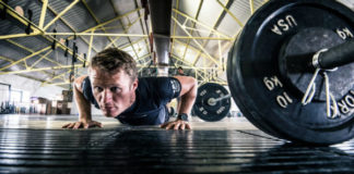 Man performs pushups in a gym while training with high volume instead of high frequency