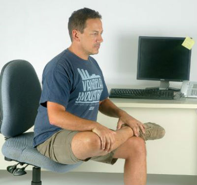 man doing seated hip stretches at work