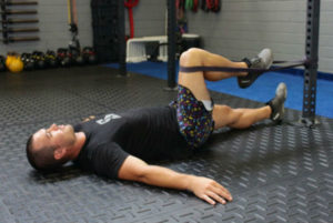 man performs a psoas hold using a band as one of his favorite sports hernia treatment exercises