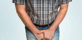 man with inguinal ligament pain symptoms holds his groin