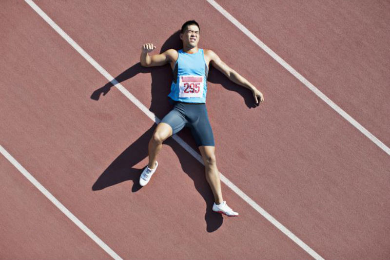 track athlete lies in pain as he waits for the personal trainer to complete his sports hernia diagnosis