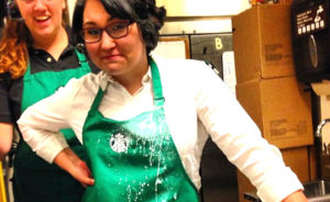 Starbucks barista stands with hands at hips after spilling keto low carb coffee drink on herself