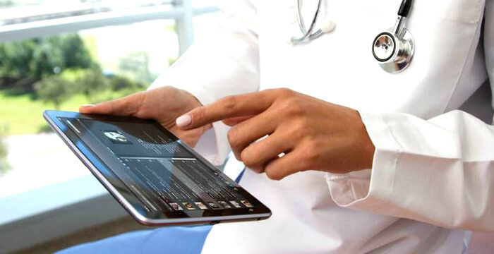 Trained specialist wearing a white lab coat uses physical therapy software for emr and billing to track and manage patient documentation