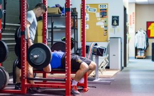 Spotter helps lifter perform a bench press pyramid program to increase strength