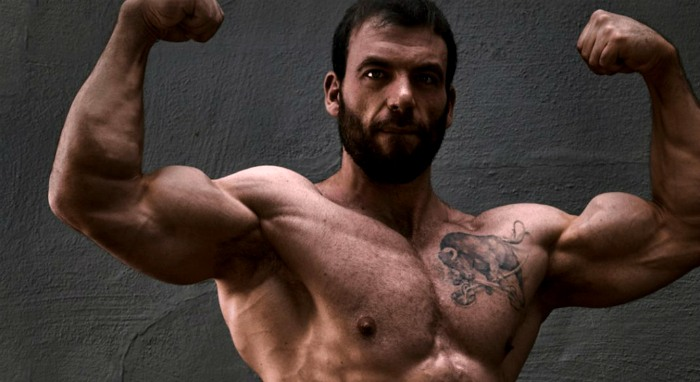 ben pollack, one of the strongest and most elite lifters to use powerlifting program for mass, performing a front double bicep pose