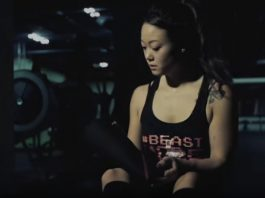 Woman Powerlifter puts on SBD knee sleeves before squatting