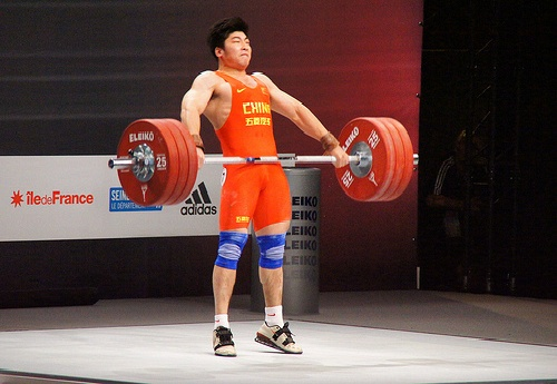 olympic lifter performs second pull during a power clean in competition