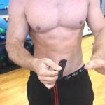 Man puts on powerlifting wrist wraps before an upper-body workout at the gym