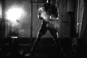 Powerlifter uses chalk to prepare for first set of sumo deadlifts following the 5-day variation of nSuns 531 CAP3