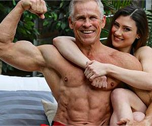 A guy who is jacked and tan flexing with a girl hugging him